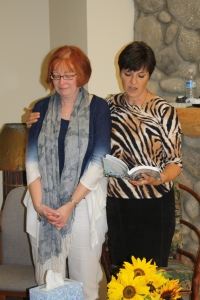 Henriet anoints Ardis' book and future speaking, September 2012.