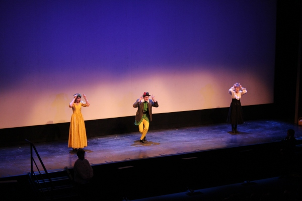 "The announcer and his assistants demonstrate gestures for ""Do, Re, Mi""."